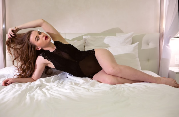 Charmante vrouw in een zwarte sexy romper liggend op het bed