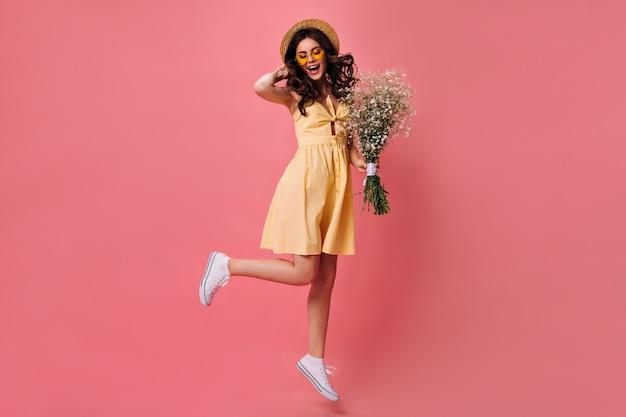 Charmante vrouw in gele jurk springt op roze muur en houdt boeket vast