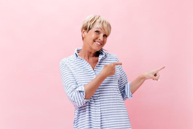 Charmante vrouw in geruite outfit wijst naar plaats voor tekst op roze achtergrond