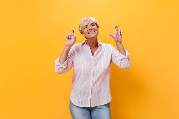 Charmante vrouw in geruite overhemd kruist vingers op oranje achtergrond
