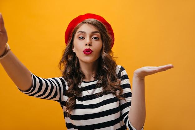 Charmante vrouw in gestreept overhemd en baret klappen kus en neemt selfie. mooi meisje met rode heldere hoed in moderne blouse op zoek naar camera.