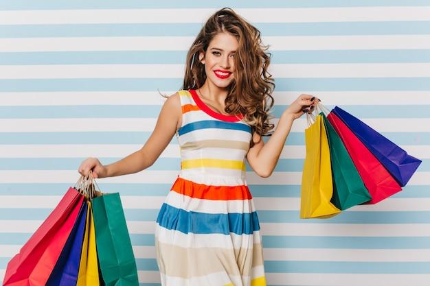Charmante vrouw in gestreepte zomerjurk poseren na het winkelen. binnenfoto van vrolijke vrouwelijke shopaholic.