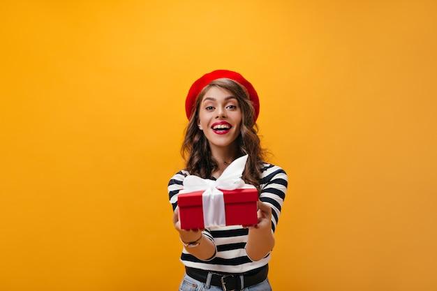 Charmante vrouw in goed humeur houdt rode doos op oranje achtergrond. aantrekkelijk meisje met heldere lippen in gestreept overhemd verheugt zich op geschenk.