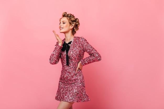 Charmante vrouw in korte jurk poseren op roze muur en kus verzenden