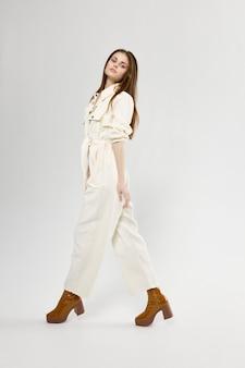 Charmante vrouw in lichte jumpsuit en laarzen mode-stijl zijaanzicht