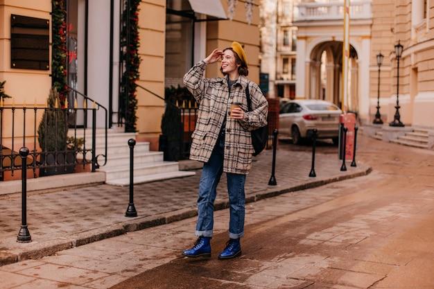 Charmante vrouw in oversized jas met glimlach kijkt in de verte