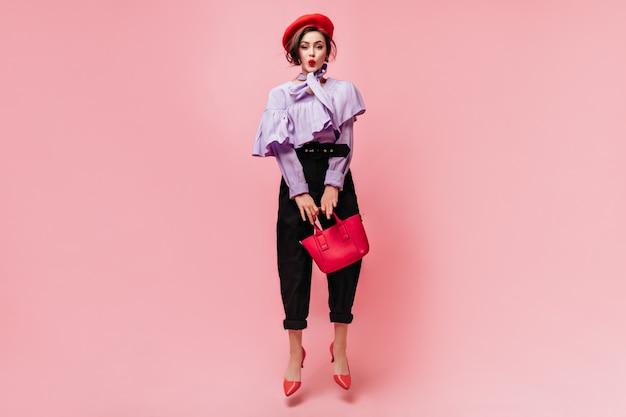 Charmante vrouw in paarse blouse en zwarte broek fluit, houdt rode tas en springt.