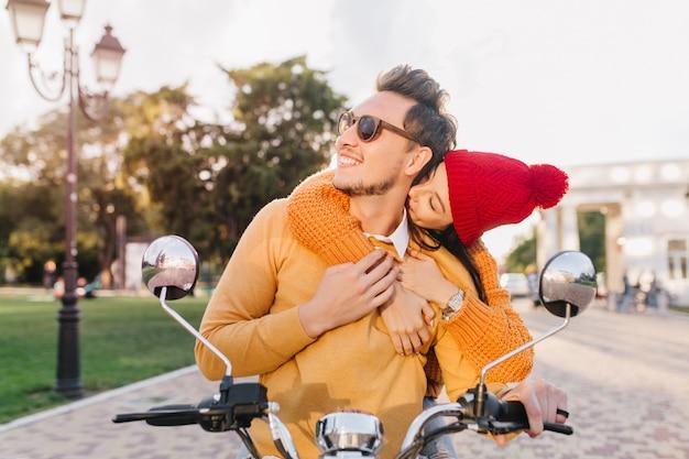 Charmante vrouw in rode hoed kussen vriendje nek zittend op scooter