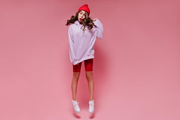 Charmante vrouw in rode korte broek en oversized paarse hoodie springt op geïsoleerd