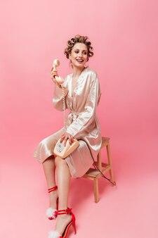 Charmante vrouw in roze gewaad glimlacht, zit op een stoel en houdt telefoon vast op geïsoleerde muur