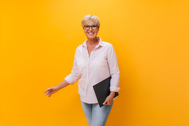 Charmante vrouw in roze outfit en bril poseren met papieren tablet