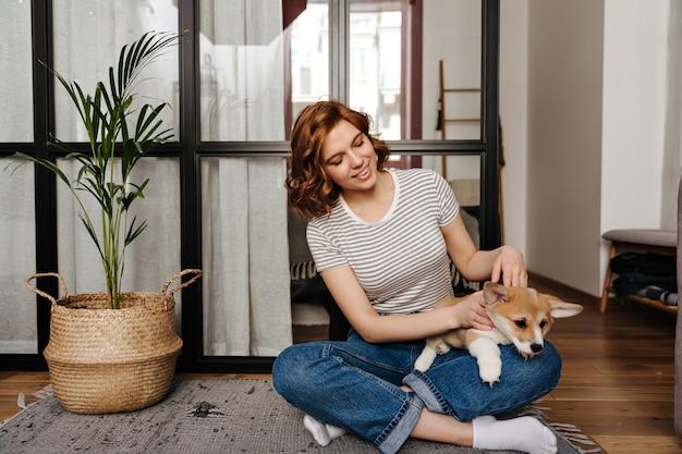 Charmante vrouw in spijkerbroek rust in de woonkamer en speelt met de hond.