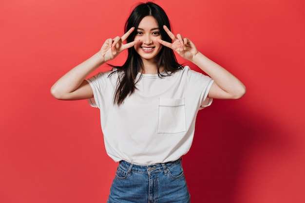 Charmante vrouw in stijlvol t-shirt glimlacht en vredestekens vertoont