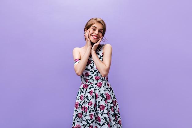 Charmante vrouw in stijlvolle jurk vormt op paarse achtergrond. aantrekkelijk schattig meisje in heldere kleurrijke kleding met glimlach op zoek naar camera.