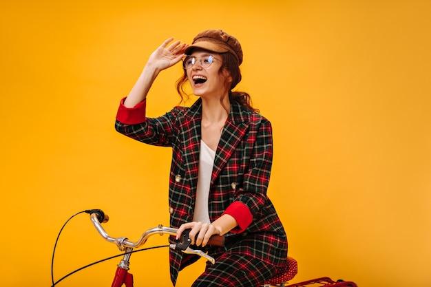 Charmante vrouw in trendy pet en klassen fietst op oranje muur