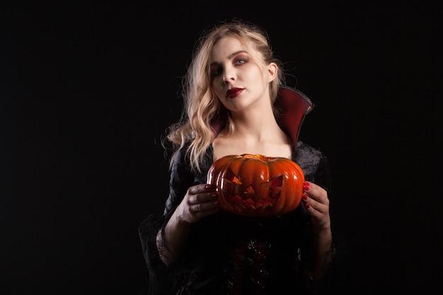 Charmante vrouw in vampierkostuum die halloween-pompoen op donkere achtergrond houdt. stijlvolle vampiervrouw.