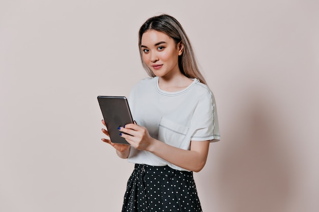 Charmante vrouw in wit de computertablet van de t-shirtholding
