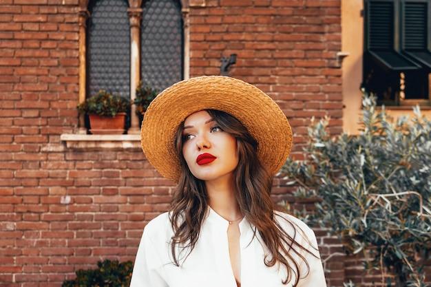 Charmante vrouw in witte blouse en strohoed. portret van make-up meisje met lang haar en grote rode lippen. make-upkit, zomersfeer, concept van pure perfecte huid. schoonheid vakantie concept