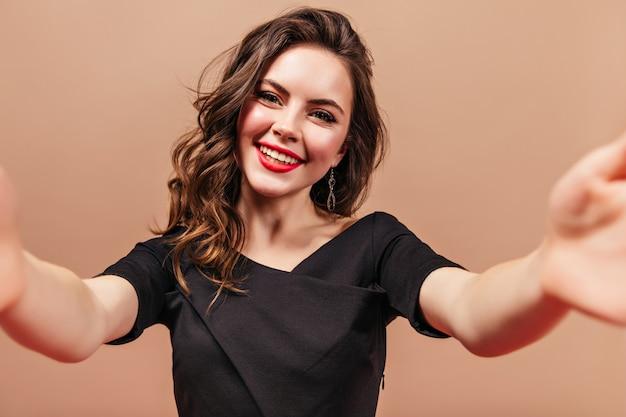 Charmante vrouw in zwarte blouse maakt selfie op beige achtergrond. portret van meisje met rode lippenstift.