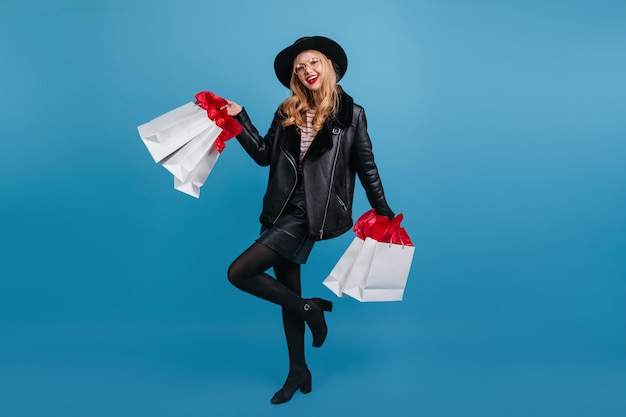 Charmante vrouw in zwarte kleding met boodschappentassen. vrij blond meisje in hoed en lederen jas dansen op blauwe muur.