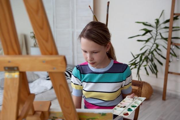 Charmante vrouw kunstenaar schildert enthousiast een foto zittend aan een ezel