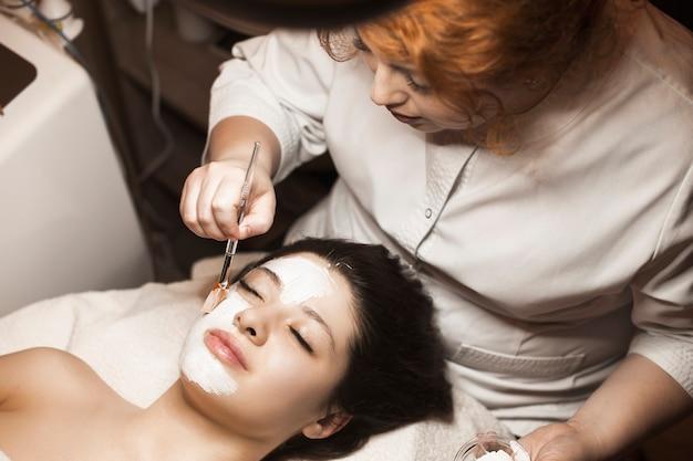 Charmante vrouw, leunend op een bed met gesloten ogen, heeft een skin-kare routine terwijl ze een wit masker op haar gezicht aanbrengt in een wellnessresort.