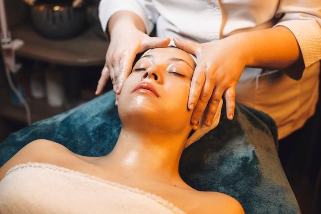 Charmante vrouw leunend op een spa-bed met gesloten ogen terwijl ze een gezichtsmassage heeft met een huidverzorgingsmasker op haar gezicht in een spa-centrum.