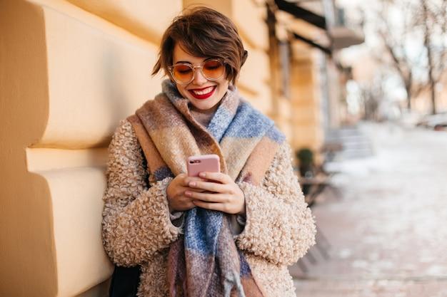 Charmante vrouw met behulp van smartphone op straat