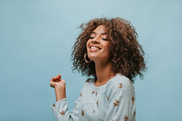 Charmante vrouw met donkerbruin kort haar in stijlvolle gouden oorbellen en bedrukte blauwe kleding glimlachend met gesloten ogen op geïsoleerde muur..