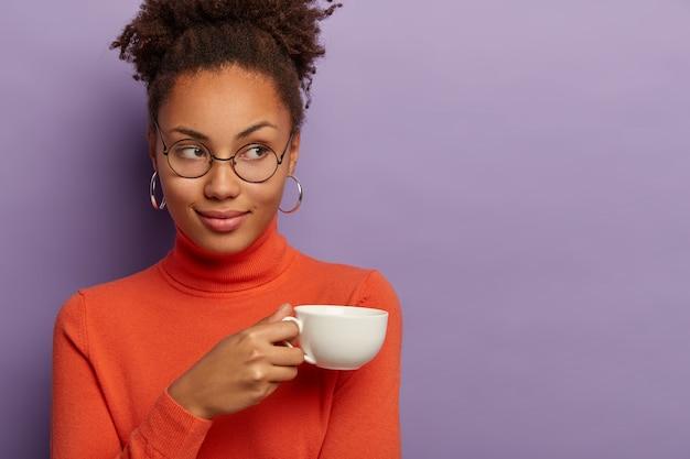 Charmante vrouw met donkere huid en krullend haar, drinkt koffie of thee, houdt witte mok vast, draagt een bril en oranje coltrui