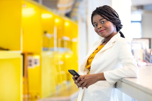 Charmante vrouw met een donkere huidskleur staat in de buurt van de balie, gebruik de telefoon, draag een geel shirt binnenshuis op kantoor, een gelukkige glimlach afro-amerikaanse vrouw met een telefoon die op de werkplek staat