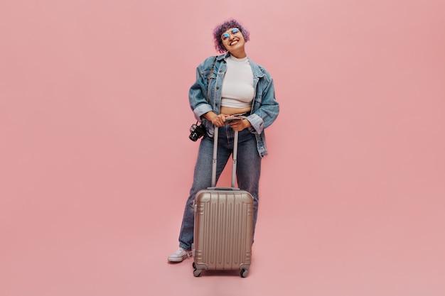 Charmante vrouw met een glimlach op haar gezicht in een oversized spijkerjasje, een strakke broek en een witte bovenkant houdt koffer en camera op roze.