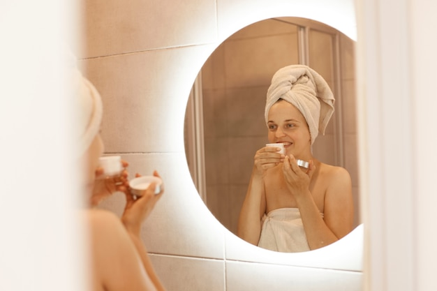 Charmante vrouw met een perfecte huid ruikende crème en kijkend naar haar spiegelbeeld in de badkamerspiegel, staande met blote schouders en witte handdoek op haar hoofd.
