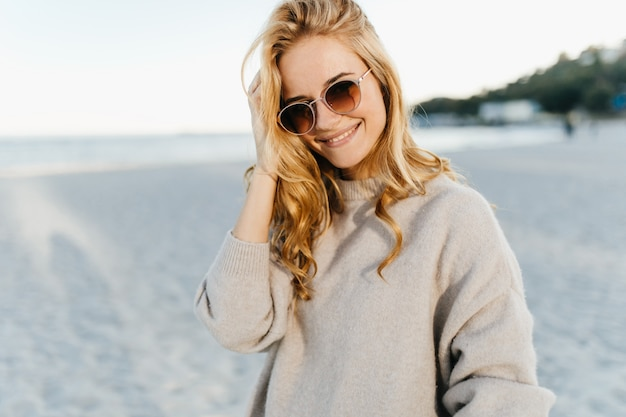 Charmante vrouw met golvend blind haar, gekleed in lichte trui en zonnebril met glimlach tegen zee.