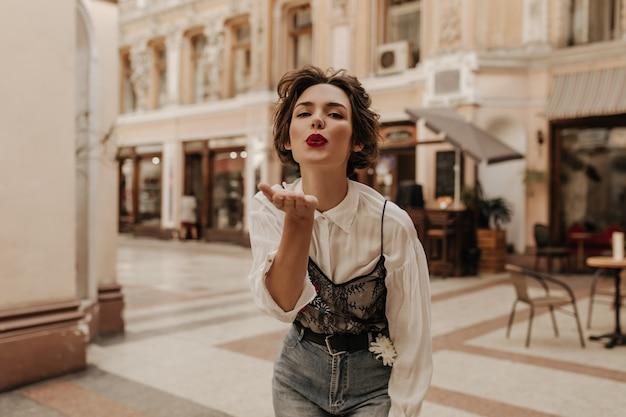 Charmante vrouw met golvend haar in shirt met kant en spijkerbroek waait kus op straat. donkerbruine vrouw met rode lippen die in stad stellen.