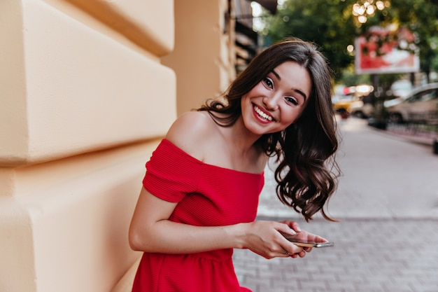 Charmante vrouw met golvend haar staande in de buurt van de telefoon te bouwen en vast te houden. donkerharige blithesome meisje in een rode jurk lachen naar de camera.