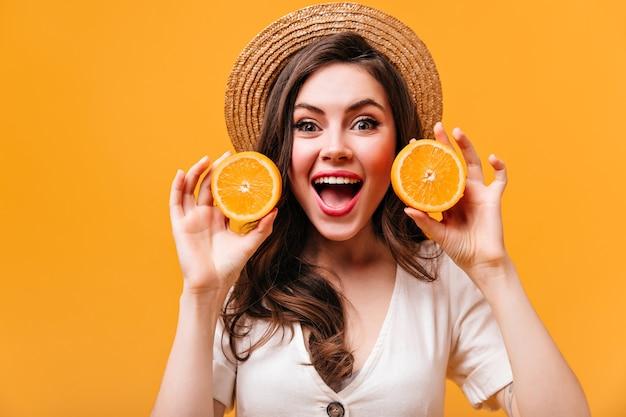 Charmante vrouw met groene ogen kijkt met verrukking in de camera en houdt sinaasappelen op geïsoleerde achtergrond.