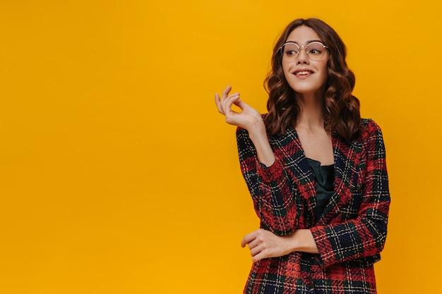 Charmante vrouw met krullend haar in brillen poseren op geïsoleerde muur