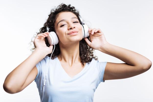 Charmante vrouw met krullend haar in een wit t-shirt, luisteren naar de muziek in de koptelefoon en glimlachen terwijl geïsoleerd op grijs