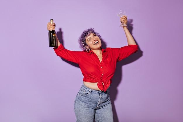 Charmante vrouw met paars haar in shirt en spijkerbroek lacht met glas in zijn hand. prachtige dame in lichte kleren houdt fles wijn.
