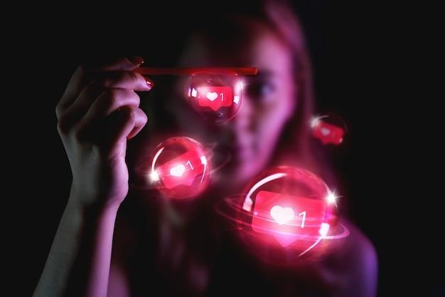 Charmante vrouw met tekens in de vorm van likes van sociaal netwerk in zeepbellen - neonroze licht