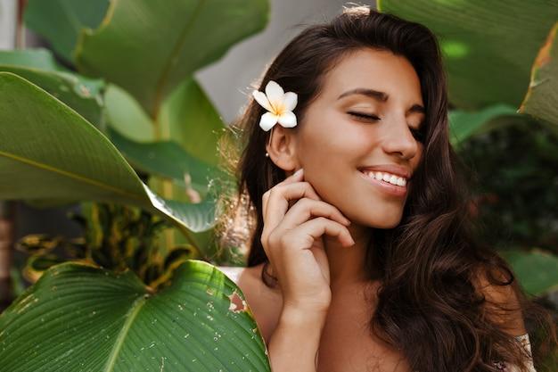 Charmante vrouw met witte bloem in donker haar glimlacht lief met gesloten ogen tussen tropische boom met grote bladeren