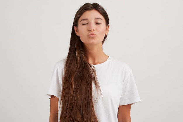 Charmante vrouw, mooi meisje met donker lang haar, gekleed in een wit t-shirt