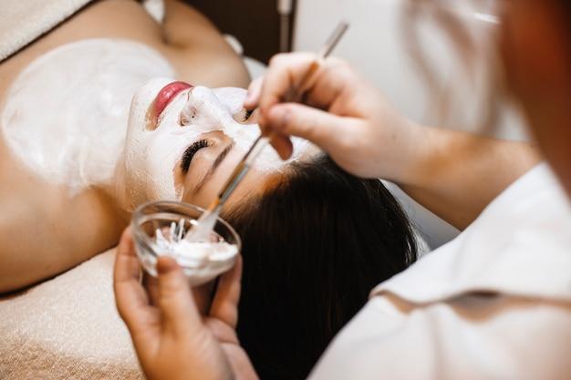 Charmante vrouw ontspannen na het werk in een wellness-spa die gezichtsprocedures doet.
