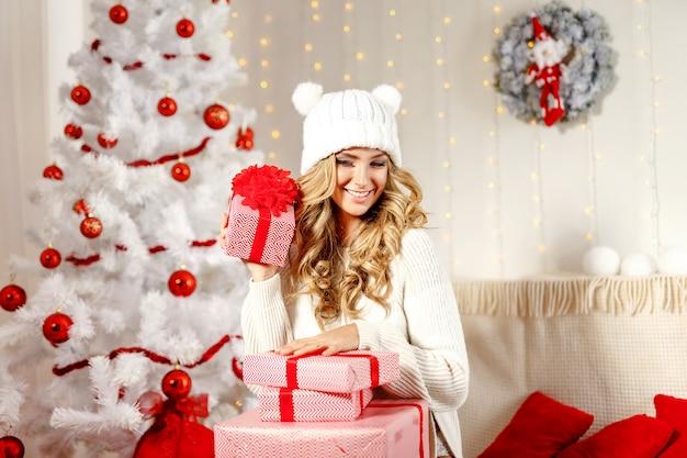 Charmante vrouw poseren met kerstcadeautjes