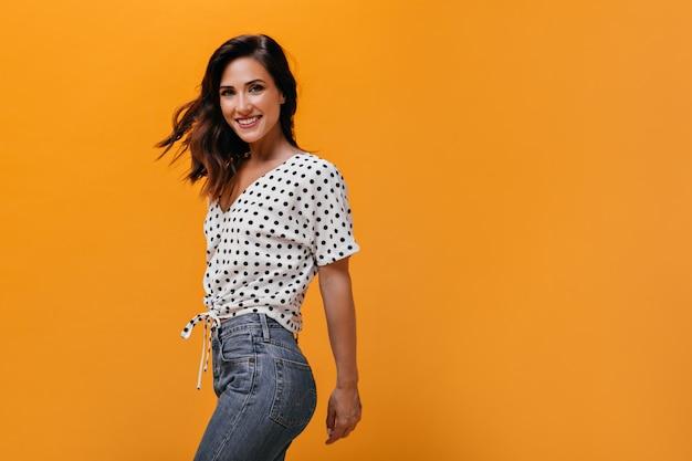 Charmante vrouw schakelt oranje achtergrond in. leuk meisje in goed humeur met kort haar in polka-dot shirt en in lichtblauwe spijkerbroek lacht.