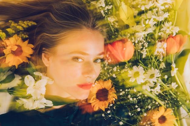 Charmante vrouw tussen verse bloemen in groenheid