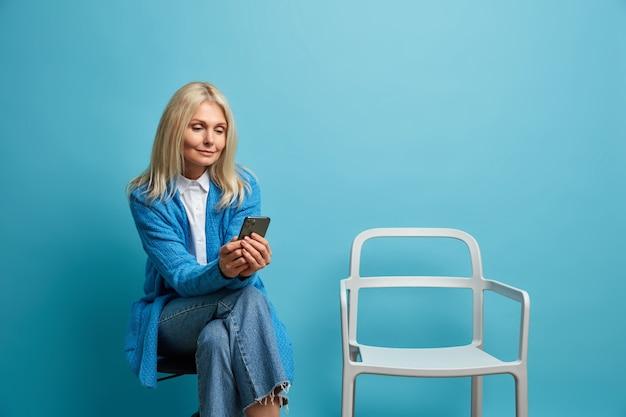 Charmante vrouw van middelbare leeftijd zit in de wachtrij in de buurt van kabinet vormt op stoel tegen blauwe muur, maakt gebruik van smartphone