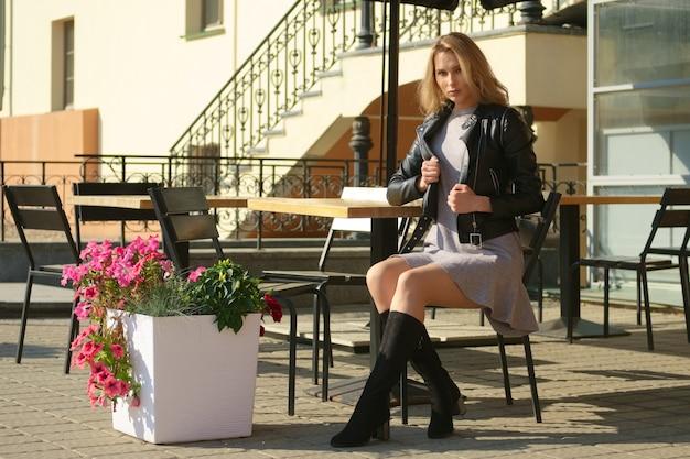 Charmante vrouw zit op houten kruk op open terras van straat caffe