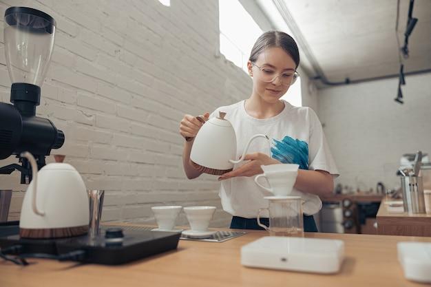 Charmante vrouwelijke barista die filterkoffie maakt in cafetaria
